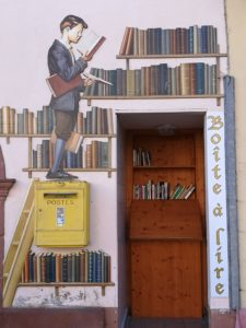 Das Bild zeigt einen öffentlichen Bücherschrank in Ribeauvillé in Frankreich an. Es ist eine Wand zu sehen, auf die ein Bücherregal gemalt ist. An der Wand ist ein Briefkasten befestigt. Es sieht so aus, als ob ein Junge auf diesem Briefkasten steht, aber der Junge ist auch auf die Wand gemalt. Er steht auf einer Leiter und er hält ein Buch in der Hand und liest. In der Mauer ist eine Vertiefung, dort ist der öffentliche Bücherschrank. Hier stehen einige Bücher in einem Regal.